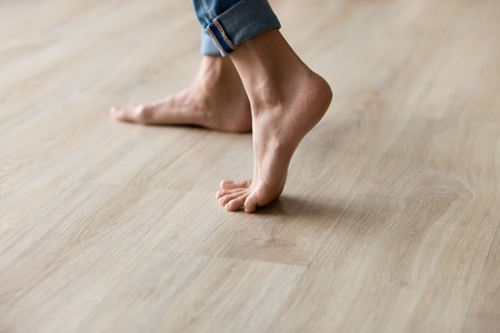 Side close up view of unrecognizable woman feet legs, barefoot girl standing indoors inside of modern home enjoy warm wooden heated floor, perfect groomed body part pedicure services spa salon concept Archivio Fotografico