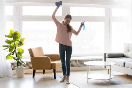 La donna a figura intera in abiti casual balla la pulizia della casa tiene il detersivo per flaconi spray per stracci blu si sente felice, qualificata agenzia specializzata nelle pulizie che assume, concetto di faccende domestiche veloce e facile