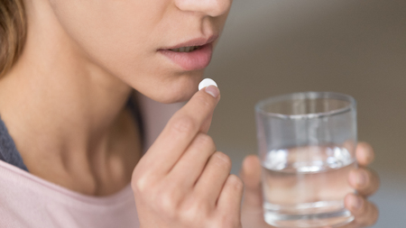 Close up image woman holding round pill and glass of still water taking painkiller to relieve painful feelings migraine headache, antidepressant or antibiotic medication, emergency treatment concept Foto de archivo