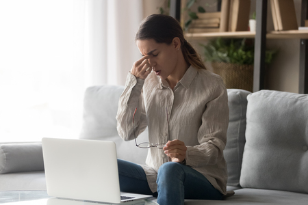 Woman sitting on couch at home near laptop takes break from working or study feels tired rubbing dry irritated eyes taking off glasses reduce eye strain, long period computer usage poor vision concept Stock fotó