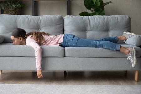 Toute la longueur d'une fille allongée se reposant à la maison dans le salon enfouie son visage dans le canapé ressent de l'épuisement après une sieste le jour manque d'énergie après la fête nuit blanche ou surmenée, trop fatiguée sans concept de motivation Banque d'images