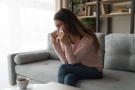 Unhealthy allergic woman sitting on couch holding paper tissue wiping her runny nose, girl with broken heart crying feels unhappy desperate, break up, split with boyfriend, personal problems concept