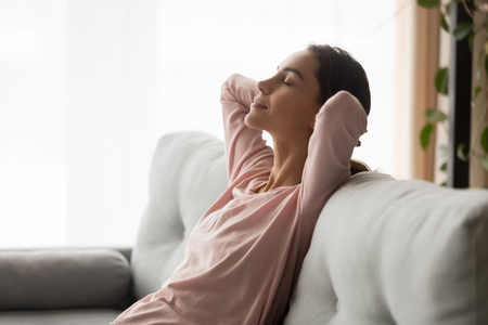 Vista ravvicinata laterale serena giovane donna tiene le mani dietro la testa gli occhi chiusi si sente placidità, ragazza tranquilla che fa un pisolino di giorno appoggiata su un comodo divano in soggiorno, ristoro e concetto di sogno ad occhi aperti
