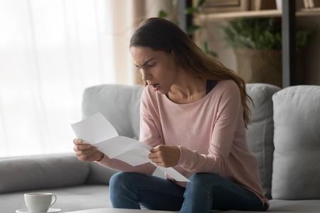 Donna arrabbiata seduta sul divano a casa con in mano una lettera che legge notizie terribili sul rifiuto del lavoro aziendale si sente frustrata emozioni negative espressioni del viso, ammissione al college o concetto di rifiuto del prestito bancario