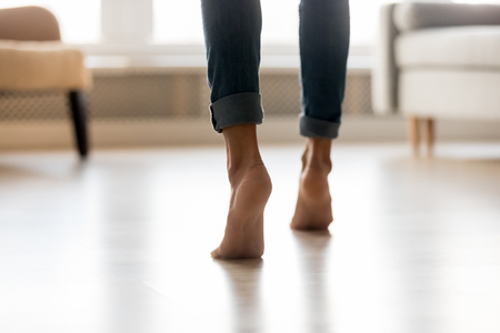 Rear view close up cropped image caucasian barefoot woman feet in blue jeans, female stands on tiptoes enjoys modern home warm electric underfloor heating or active girl moving dancing indoors concept