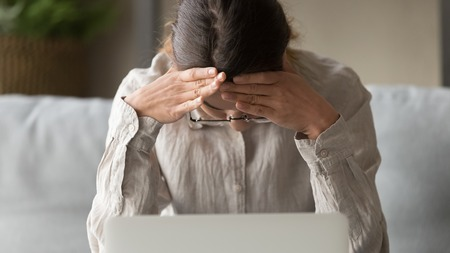 Close up woman sitting on couch at home in front of laptop looks down hold head with hands feels desperate having serious problems, bad news debt bankruptcy dismissal or suffers from headache concept