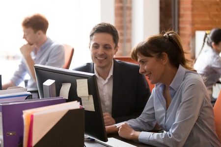 Smiling diverse businesspeople sit at office desk work together at pc discuss company project, happy female and male employee, man and woman brainstorm collaborating at computer in shared office Stock Photo