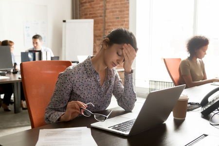 Tired young indian female worker take off glasses feeling unwell suffer from migraine or headache, exhausted sick woman employee touch head have blurry vision or dizziness in shared office