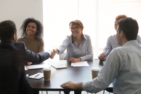 Diverse businesspeople shake hand congratulating with successful negotiations closing deal or sign agreement, business partners handshake greeting introducing get acquainted at meeting
