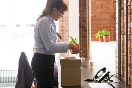 Happy hired middle aged female employee take off plant settle at new workplace office desk, excited employed woman newcomer worker unpack cardboard box start job unbox things on first working day Stock Photo - 122368284