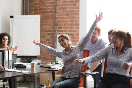 Excited multiracial employees have fun during break smiling riding on chairs in shared office, happy diverse colleagues laugh entertaining at workplace enjoy playing funny game activity together Фото со стока
