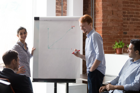 Multiracial millennial presenters speak explaining project to colleagues draw on flipchart, smiling diverse employees make whiteboard presentation brainstorming in office cooperating with coworkers