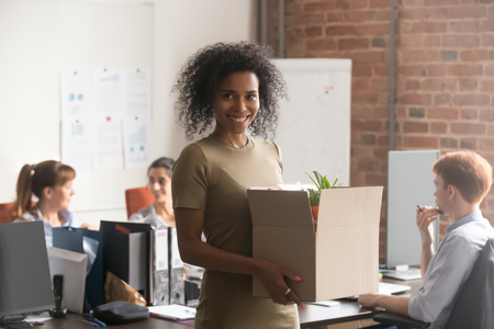 Smiling african American female newcomer holding box with personal belongings posing on first work day, happy excited black woman newbie or intern take picture ready to unpack settle at new workplace