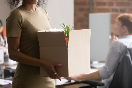 Close up of millennial african American female intern or newcomer stand holding cardboard box with personal belongings, black woman newbie worker first day in new office settle at workplace 写真素材