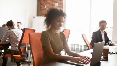 Smiling african American millennial employee sit at desk working on laptop consult client online in shared office, happy positive black woman worker busy typing email to customer in coworking space Stok Fotoğraf