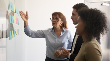 Middle aged female team leader talk explain project to multiracial team with sticky notes on office wall, businesswoman brainstorm with diverse colleagues negotiate discuss plan working with stickers Banco de Imagens