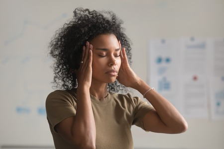 Close up of exhausted african American woman feel unwell touch massage temples suffer from headache, tired black female worker have migraine or dizziness stand with eyes closed. Health problem concept