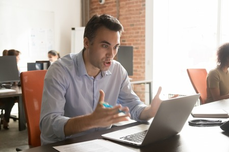 Angry male worker scream looking at laptop screen annoyed with slow internet connection, furious man employee yell feel mad bothered with computer breakdown, spam or system malfunction Stock Photo