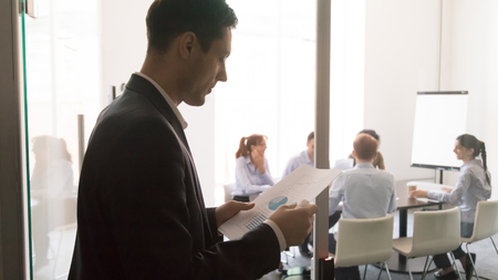 Worried male worker stand outside conference room reading paperwork project report get ready for presentation, focused anxious man speaker prepare looking through paper notes before entering meeting Stock Photo
