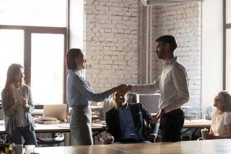 La stretta di mano dell'amministratore delegato dell'azienda si congratula con la giovane donna con un lavoro e una promozione di successo, sostenendo, apprezzando i buoni risultati o gratificando mentre il team aziendale multietnico si è riunito in ufficio