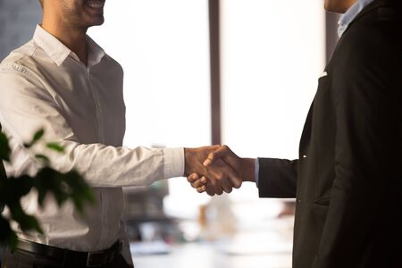 Two businessman standing at office start negotiations shaking hands, close up. Black employer HR manager applicant new employee vacancy candidate handshaking, gesture of greeting trust respect concept