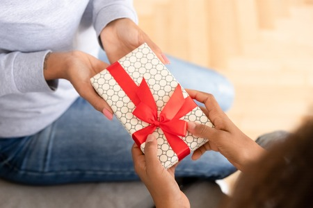 Close up African American teen girl presenting gift box to mother, teenage daughter making surprise for mum, family celebrating birthday or mothers day, female hands holding gift box with bow Stock fotó