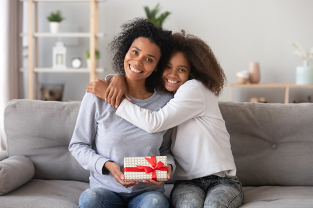 Head shot portrait of smiling African American mother received gift from teenage daughter, happy teen girl embracing mum holding box, posing for photo together, sitting on couch, looking at camera