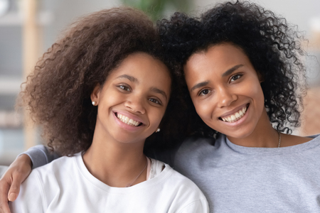 Head shot portrait of happy excited African American mother and teen daughter, looking at camera, posing together for family photo at home, smiling black mum and teenage girl, child embracing