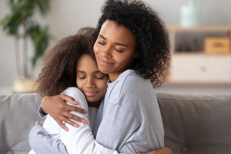 African American mother and teenage daughter embracing, enjoying moment together, sitting with closed eyes on couch at home, trusted relationships between mom and teen girl, showing love and care