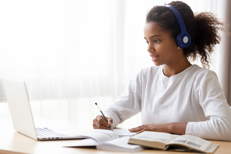 African American teen girl wearing headphones learning language online, using laptop, looking at screen, doing school tasks at home, writing notes, listening to lecture or music, distance education