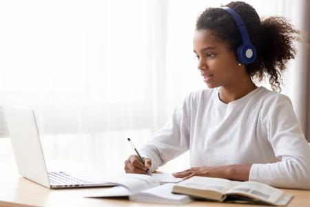 Afroamerykanka w słuchawkach, ucząca się języka online, korzystająca z laptopa, patrząca na ekran, wykonująca zadania szkolne w domu, pisząca notatki, słuchająca wykładu lub muzyki, nauczanie na odległość Zdjęcie Seryjne