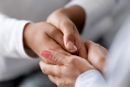Close-up zorgzame Afro-Amerikaanse moeder die de handen van het kind vasthoudt, liefde en steun toont, zwarte moeder troostend, strelend kind, kinderbeschermingsconcept, familie genietend van moment samen
