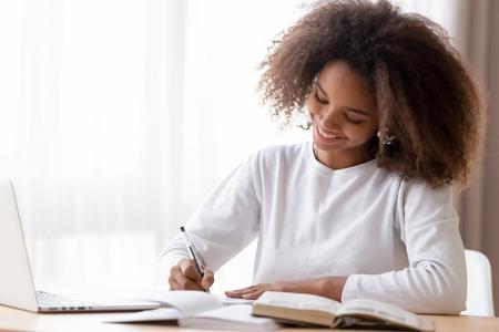 Lächelndes afroamerikanisches Teenager-Mädchen, das Schulhausaufgaben vorbereitet, Laptop verwendet, glückliches schwarzes Schulmädchen, Schüler, die Aufgaben erledigen, Aufsätze schreiben, zu Hause lernen, Notizen machen, schreiben, Lehrbücher lesen Standard-Bild
