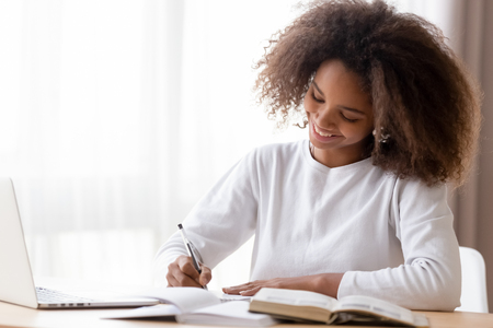 Smiling African American teen girl preparing school homework, using laptop, happy black schoolgirl, pupil doing tasks, writing essay, studying at home, making notes, writing, reading textbooks Stockfoto