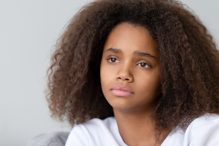 Close up upset thoughtful African American teenage girl sitting alone, looking in distance, thinking about teen problem, first love or trouble at school with friends or parents, feeling unhappy
