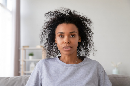 Head shot portrait of African American woman making video call, looking at camera, talking, using webcam, vlogger recording vlog, internet teacher tutor working at home, online job interview Foto de archivo