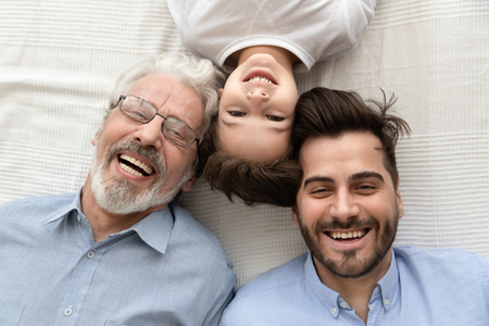 Top view of happy three generations of men lying on bed looking at camera making photo together, portrait of smiling little son, father and grandfather posing for picture laughing relaxing at home