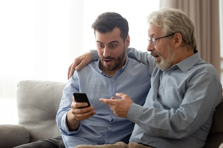 Millennial man and senior dad sit on couch at home feel surprised reading news on smartphone, amazed elderly father with grown son shocked by information or promotion using cellphone together