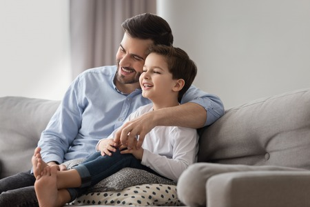 Happy young dad and smiling little son sit on sofa together relax on comfortable furniture in living room, loving father cuddle hug preschooler boy child have fun laughing enjoying weekend at home Standard-Bild - 123628503