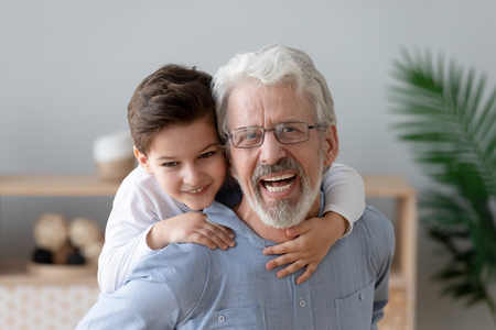 Portrait of playful little boy piggyback smiling grandfather enjoy having fun together at home, happy grandparent play with preschooler grandchild, carry him on back relaxing looking at camera
