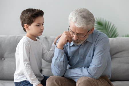 Little boy sit on couch caress sad grandfather showing support and understanding toward old, cute preschooler grandchild touch comfort upset grandparent feel sorry make peace reconcile after fight