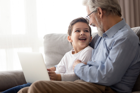 Happy preschooler boy child relax sit on couch with loving grandfather using laptop together, smiling grandparent and grandson spend leisure time have fun playing or watching video on computer at home Stock fotó