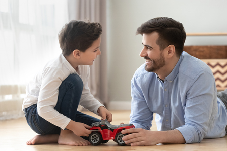 Happy father and son lying on floor have fun playing with toy car racing together, smiling dad and boy child relax at home engaged in game, laugh enjoy family weekend leisure time spending Imagens