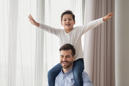 Happy preschooler boy child have fun sit on father back shoulders laugh spending time together with young parent, smiling excited dad and son play together entertain at weekend at home