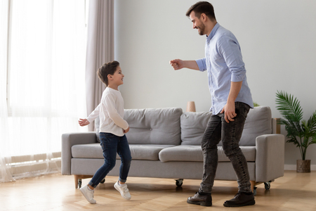 Happy millennial father and preschooler son have fun dancing together entertaining in living room, excited young dad and little boy child enjoy family leisure activity, jump relax at home on weekend Stock Photo
