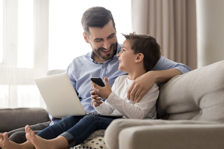 Gelukkige jonge vader zit op de bank met behulp van laptop, ontspan met kleuterzoon die smartphone vasthoudt, veel plezier samen, glimlachende vader en kleine jongenskind genieten van weekend thuis rust op de bank bezig met gadgets