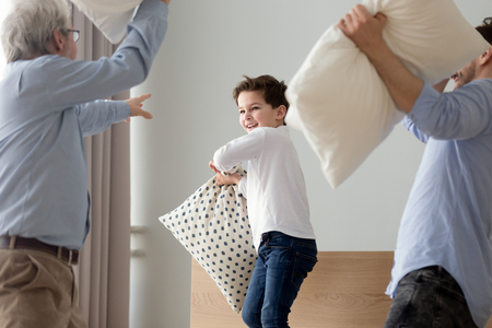 Playful little boy have fun in bedroom engaged in pillow fight with young father and grandfather, happy three generations of men feel excited play together involved in funny battle in bedroom at home