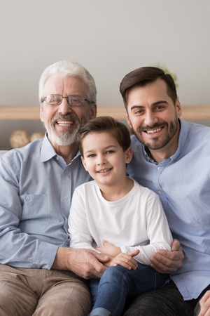 Family portrait of smiling three generations of men sit on home couch hugging looking at camera, happy grandfather, father and little son embrace posing for picture together show unity and support