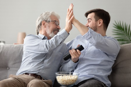 Happy elderly father and millennial son sit on couch give high five celebrating team win online game, excited young man and senior dad feel euphoric after watching TV football match together at home Stock Photo