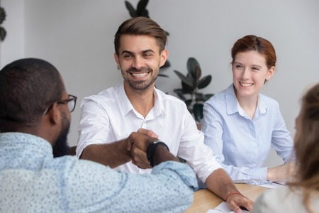 Happy smiling caucasian male manager shaking hand african-american colleague. Meeting group of businesspeople, start or completion negotiations, greeting with new effective collaboration concept